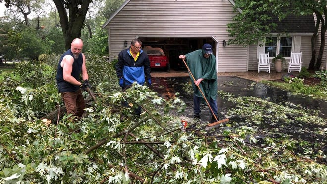 Jeffrey Witt, left, Jeff Bieck and Richard Yates clean up fallen tree limbs in their neighborhood on Kencannon Court in Rockford on Monday after a powerful storm ripped through the area.
