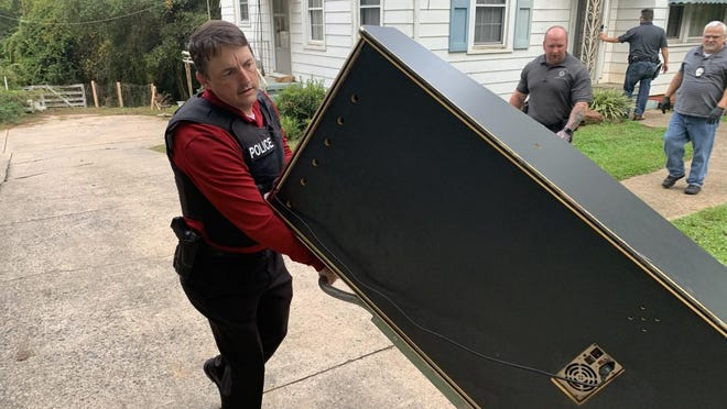 Shelby Police Lt. Scott Champion rolls out one of four machines allegedly used for gambling found during an early morning bust of two home in the 500 block of Whisnant Street in Shelby.