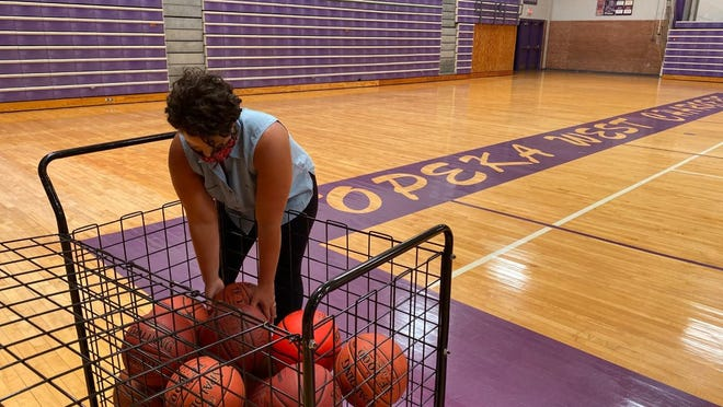 Alyx Nash, leadership studies coordinator at Topeka West High School and lead high school physical education coordinator for USD 501, sorts through basketballs Thursday afternoon in the Topeka West gym. The district's PE teachers said their classes will be a little different this year but will still focus on building students' physical and mental health.