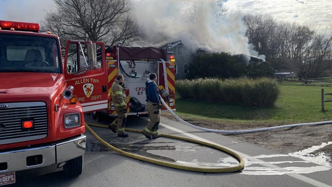Allen Township firefighters work a tanker truck to supply a Coldwater fire engine with water.