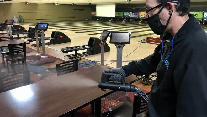 Bam facilities manager Matt Steller uses the center's new hospital-grade fogger to clean tables. The bowling center reopened Tuesday, Sept. 3, to leagues.