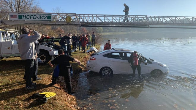 Emergency personnel work to assist Hillsdale Towing with removing a stolen car from Baw Beese Lake Sunday morning.
