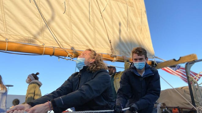 "Saugatuck High School senior Keiran Boerema and junior Max Sharnas hoist the sails on ""Serenity"" during a field trip Wednesday."