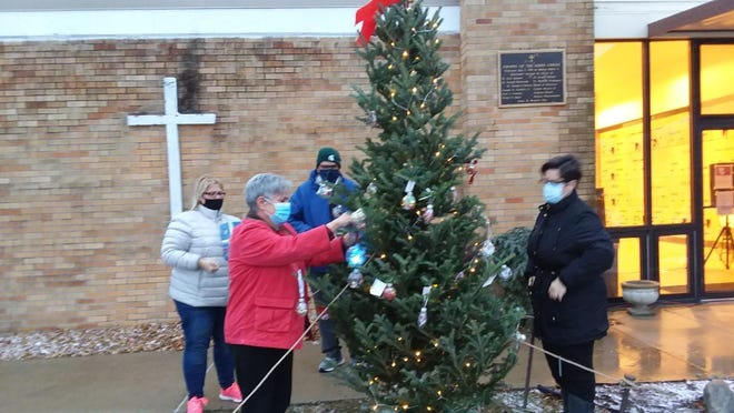 Jeanette Ryan (second from left) places a plastic lighted globe on a 10-foot-tall remembrance tree during a drive-through lighting observance Monday night in front of the Chapel of the Risen Christ at St. Joseph Cemetery. Watching are (from left) staff members Deanna Cortese, Ted Butkin and Donna VanHooser.