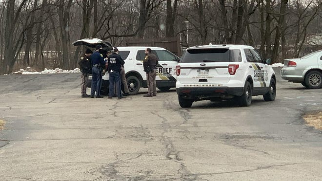 Hillsdale County Sheriff's deputies and troopers with the Michigan State Police process evidence behind the Health Department where the suspect in a stabbing was taken into custody Saturday.