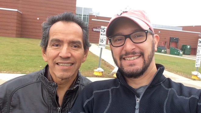 Carlos Munoz Sr. of Fond du Lac and his son, Carlos Jr., stand outside Fond du Lac High School Tuesday, where the father cast his first ballot as an American citizen.
