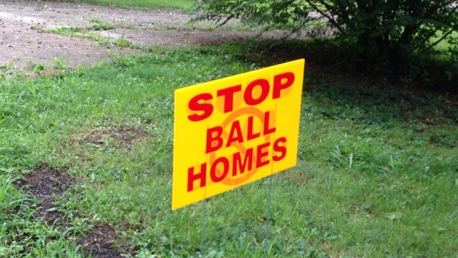 Neighbors placed signs in their yards to express their disapproval of a proposed 99-home conservation subdivision adjacent to the existing Urton Woods subdivision in August 2014.