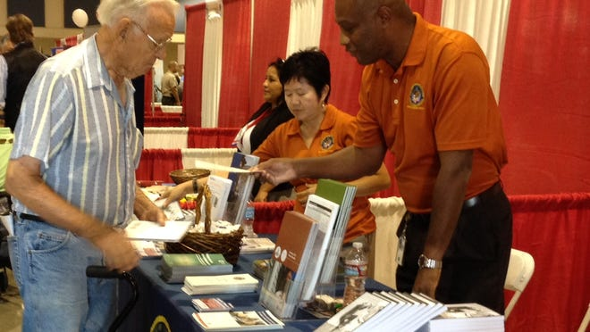 World War II veteran Leonard Cole, 90, of Indio picks up literature during the 5th Annual Veterans Expo in the Fullenwider Auditorium at the Riverside County Fairgrounds in Indio on Saturday, Oct. 11, 2014.