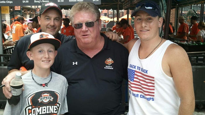 Bob Finnerty, back left, of Greece and his sons, Thomas, left, front and Jack with Baltimore Orioles legend Boog Powell at Oriole Park at Camden Yards in 2012.