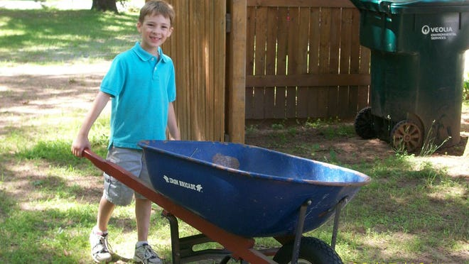 Austin Roland, a participant in Stevens Point Area Catholic Schools Summer Blast child care program, pushes a wheelbarrow while performing yard work as part of a service project.