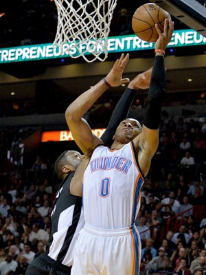 Oklahoma City Thunder guard Russell Westbrook (0) is fouled by Miami Heat guard Dwyane Wade (3) during the first half at American Airlines Arena.