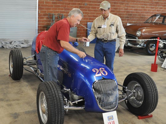 Joe Raines left, and Harris Pink prepare to remove the engine cover from a 1938 Ford Indianapolis tribute car named after a Wichita Falls racing legend, George Barringer.