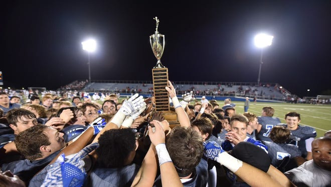 """St. Xavier hoists the """"King of the Road"""" trophy after beating La Salle 42-7 on Friday, Oct. 6, 2017"""