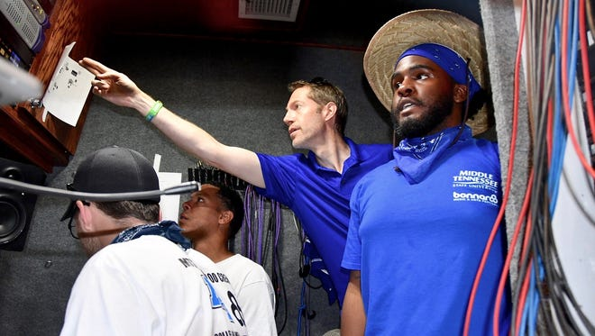 Michael Fleming (center, pointing), a professor in MTSU's Department of Recording Industry who teaches audio engineering, helps Tevin RaShad Turner (right), a graduate student in recording arts and technologies, troubleshoot audio feeds before the first concert Saturday on the Who Stage at the 2018 Bonnaroo Music and Arts Festival. Turner is the audio team leader for MTSU's work at Bonnaroo this year.