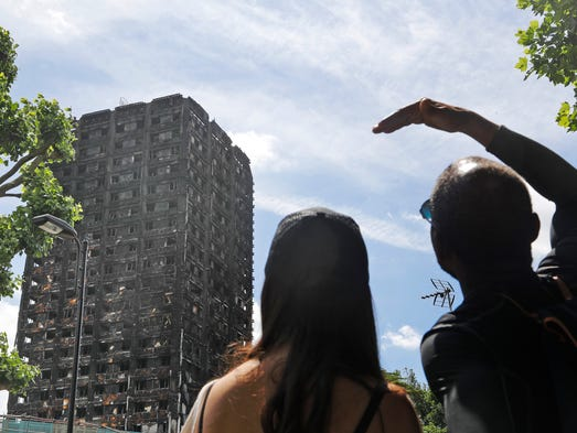 People look at the burnt Grenfell Tower apartment building