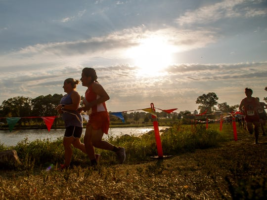 Guide Corrie DeMuth, left, runs with Wendy Flores,