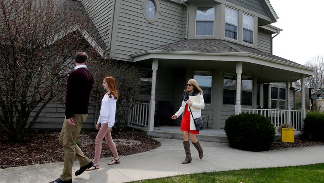 First Weber Realtor Mary Deeken, right, shows a home to the buyers of a newly sold home in Menomonee Falls on April 12, 2017.