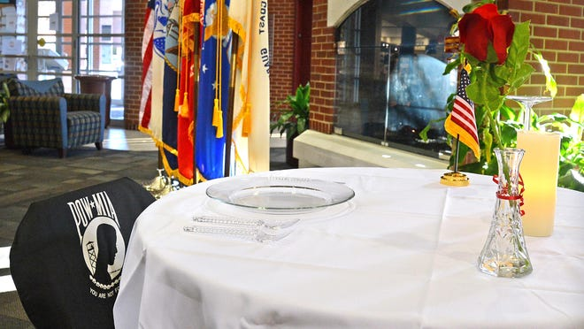 The U.S. flag and military branch flags along with a table set for one are placed inside the University of Arkansas at Fort Smith campus center for Veterans Day on Wednesday, Nov. 11. James Moore, Student Veterans Organization president, said the table is placed as a POW/MIA Remembrance. The lone chair symbolizes that members of our armed forces are missing.
