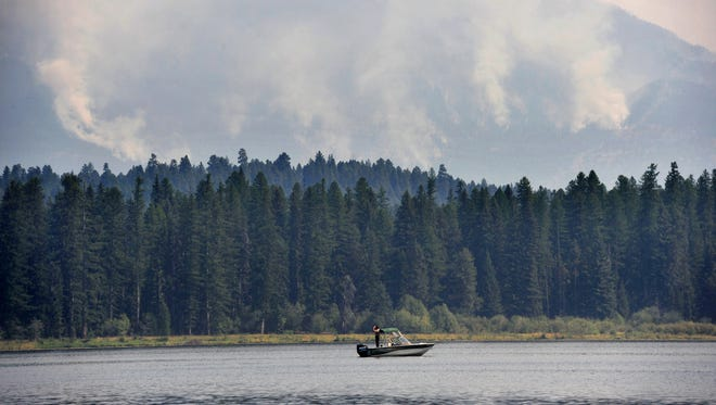 A law enforcement officer patrols Seeley Lake as fire fighting helicopters fill their water tanks to battle the Rice Ridge Fire in 2017.