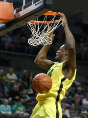 Oregon's Elgin Cook slam dunks the ball during their game with the Washington in Eugene.