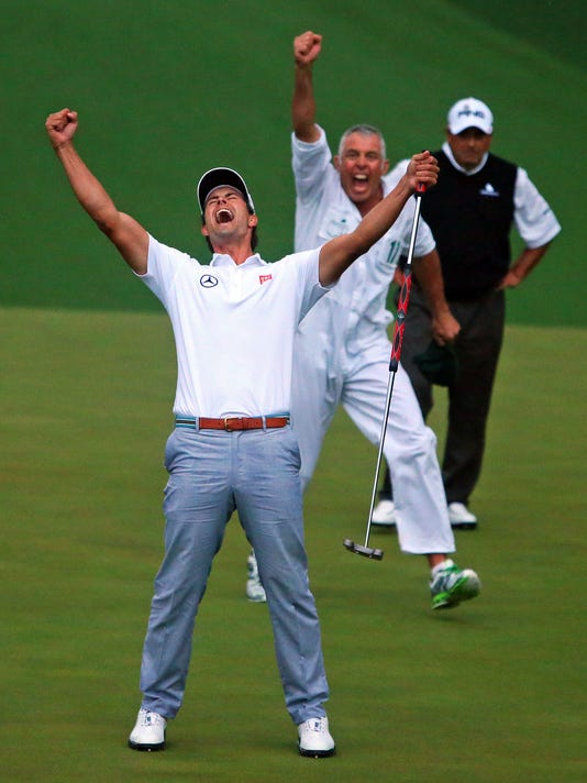 File-This April 14, 2013, file photo shows Adam Scott and his caddie Steve Williams reacting to his putt dropping on the second hole of a playoff to win the Masters golf tournament in Augusta.  (AP Photo/Atlanta Journal-Constitution, Curtis Compton)