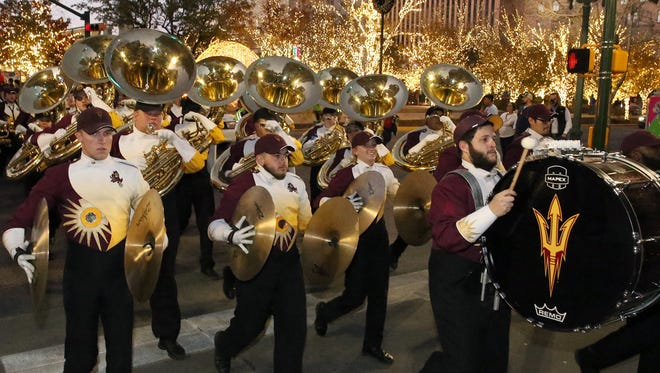 The Arizona State Sun Devils band marches along Oregon Street at San Jacinto Plaza during the Hyundai Sun Bowl Fan Fiesta Thursday at the El Paso Convention Center in downtown El Paso. The ASU and North Carolina Wolfpack bands paraded along downtown streets before they squared off at the fiesta. A fireworks display capped the event.
