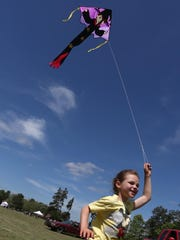 Brooklyn Schoenick, 8, of WIsconsin Rapids, runs as flies a kite at the Kiwanis sponsored Youth Outdoors Day near Wisconsin Rapids.