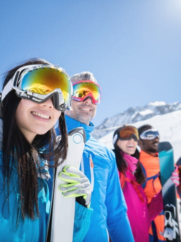 Happy group of people skiing and wearing goggles outdoors