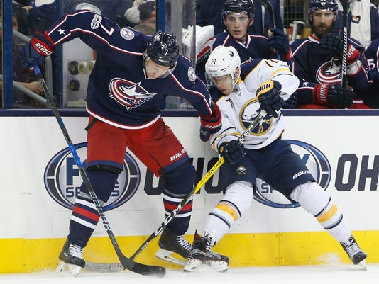 Columbus Blue Jackets' Jack Johnson, left, and Buffalo Sabres' Evan Rodrigues fight for a loose puck during the third period of an NHL hockey game Friday, March 10, 2017, in Columbus, Ohio. The Blue Jackets beat the Sabres 4-3. (AP Photo/Jay LaPrete)