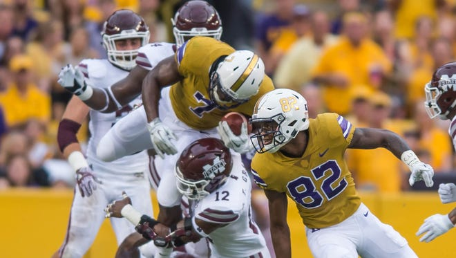 LSU Tigers running back Leonard Fournette (7) leaps over the defensive line for the first down during the first half of a SEC game between Mississippi State and the LSU Tigers in Death Valley on Saturday September 17, 2016.