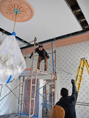 Plastic sheeting covers the chandeliers and wallpaper
