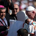 Pope Francis kisses a baby from his popemobile in San Cristobal de las Casas, Mexico, on Monday. Francis is celebrating Mexico's Indians on Monday with a visit to Chiapas state, a center of indigenous culture, where he will preside over a Mass in three native languages thanks to a new Vatican decree approving their use in liturgy. The visit is also aimed at boosting the faith in the least Catholic state in Mexico.