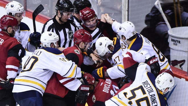 Arizona Coyotes left wing Anthony Duclair (10) and right wing Shane Doan (19) and left wing Mikkel Boedker (89) fight with Buffalo Sabres defenseman Zach Bogosian (47), and left wing Marcus Foligno (82) and defenseman Rasmus Ristolainen (55) as NHL linesman Darren Gibbs (66) tries to break them up after the conclusion of the game at Gila River Arena on Jan. 18, 2016.
