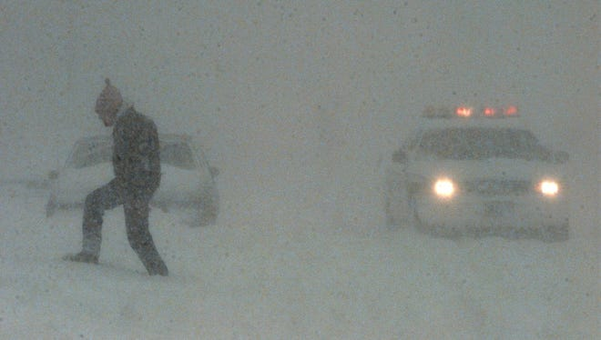 In this file photo, a lone pedestrian makes his way through the snow covered Monroe Avenue as a police car passes.