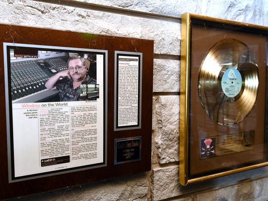 A framed magazine article and gold record hang on the wall in Bob Ketchum's studio.