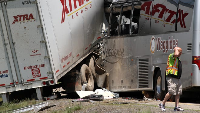 A man walks near the scene of a fatal collision between a tractor-trailer and a tour bus on Interstate 380 near Tobyhanna, Pa.