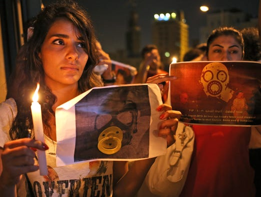 Syrian women, who live in Beirut, hold candles and placards during a vigil against the alleged chemical weapons attack on the suburbs of  Damascus, in front of the United Nations headquarters in Beirut.