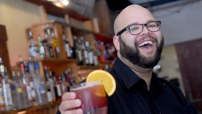 """Although Andre Brown grew up in Harrisburg, the bartender from the Revival Social Club immediately became a fan of York.  """"Coming to York, you really get a sense of a very close-knit community,"""" said Brown, who is holding up his favorite drink, the George Street Sour."""