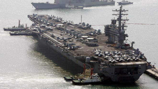 In this March 22, 2007, file photo, the U.S. aircraft carrier USS Ronald Reagan, bottom, anchors as U.S. Aegis Ship passes after they arrive at Busan port for joint military exercises in South Korea.
