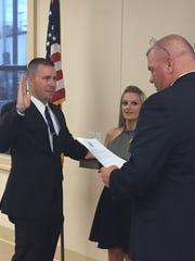 Alex Colles, left, is sworn in as a Newark Police Officer, alongside his wife, Krystal.