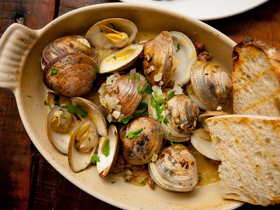 """If you don't mind sharing, which the menu encourages, order several """"Bites"""" for the table, like these clams served with toasted baguettes."""