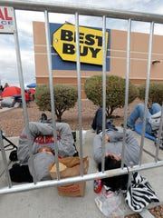 Shoppers take a nap outside Best Buy as they wait for the store to open Thursday.