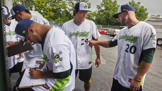 Pitcher Jordan Schwartz, right, pokes catcher Seong-min Kim as Vermont Lake Monsters players line up to have their head shots taken at Centennial Field in Burlington on Tuesday.