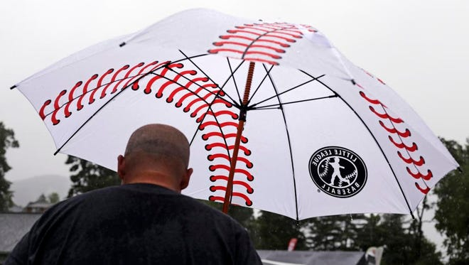 A Little League baseball fan arrives at a rainy Lamade Stadium where the Sunday games of the Little League World Series were postponed because of rain.