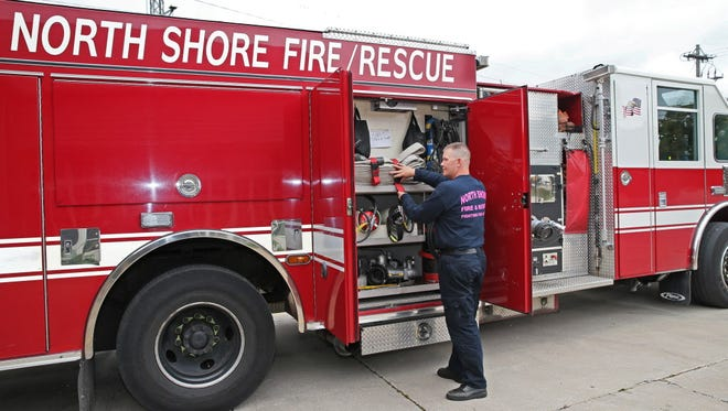 Firefighter Chris Wahlen secures gear on one of the engines at North Shore Fire/Rescue Station No. 81 in this file photograph from 2015.