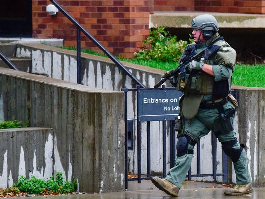An armed SWAT officer walks down Main Avenue during a standoff at the downtown Sioux Falls library on Sept. 25, 2017. The Sioux Falls Police Department says it is taking a fresh approach to how it handles SWAT calls.