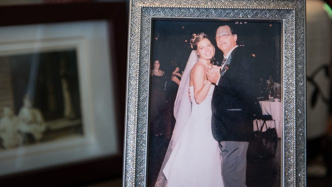 A photo of Heather Hazel and her father, Robert Miller, at her wedding is on a table at her house in Gettysburg. Miller now lives in Chile, but he left behind a memory for his daughter that reminds her of the many years she spent with him in York.