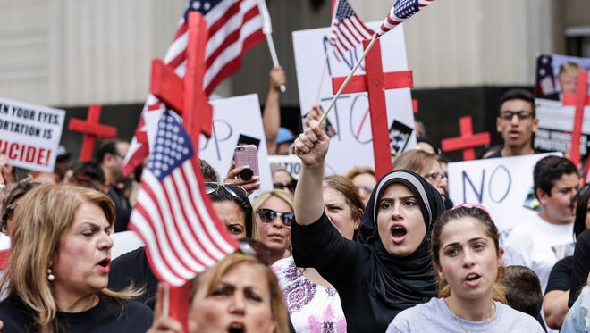 Dhona Alhaddad, of Dearborn, Mich., center right, protest the arrest of more than 100 Iraqi nationals by Immigration and Customs Enforcement outside of the Theodore Levin United States courthouse in Detroit on Wednesday, June 21, 2017.
