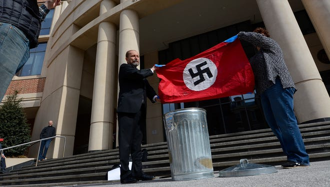 Gene Stilp, a Harrisburg activist and Democratic congressional candidate, and Holly Wertz, of Enola, Cumberland County, whose father was a prisoner of war in Germany during World War II, burn a hybrid Confederate-Nazi flag outside the York County Judicial Center, Wednesday, Feb. 28, 2018. John A. Pavoncello