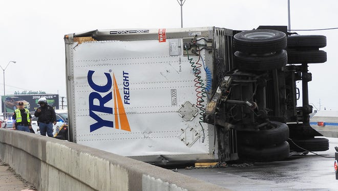 A trailer lays on its side along the West bound lanes of I-10 just West of the Chelsea overpass Saturday morning. The accident and a second one involving a jack-knifed tractor-trailer rig at I-10 West near Airway closed a section of the West-bound lanes as crews cleaned up both accidents. It is unknown if the wet weather had a role in causing the accidents.